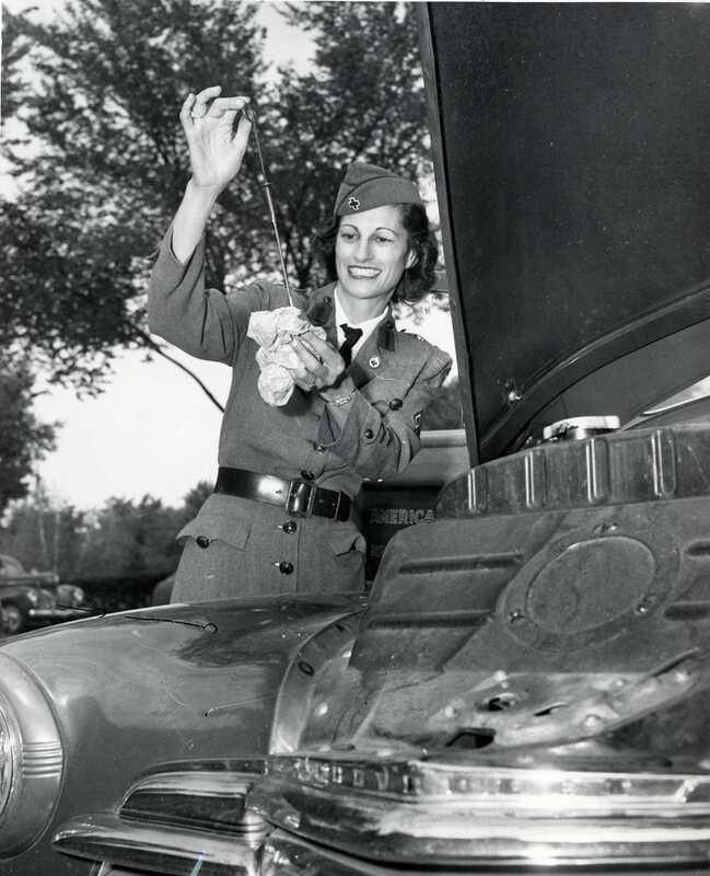 Red Cross Service Areas Motor Service ; woman in uniform checking the oil in a car