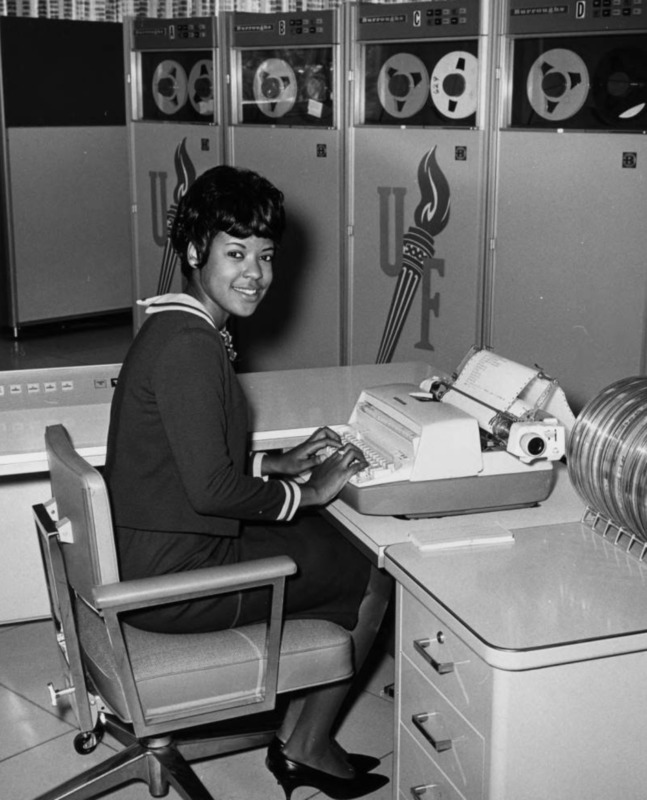 """Miss Torchy Winner; Miss Simms, the """"Miss Torchy"""" winner for 1965 United Foundation Torch Drive, at her desk. The United Fund Campaign torch cut out can be seen on two tape towers behind her."""