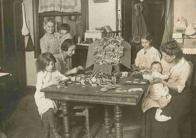 Family doing piece work in tenement ; women and children sit around a table working