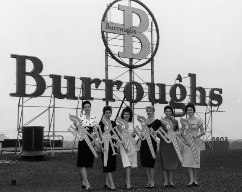 """United Foundation Campaign Promotion; Six women in dresses and high heels are standing in a row on the roof of a Burroughs building in front of the Burroughs logo and sign. Each woman poses a torch with the letter """"U' on its right and """"F"""" on its left."""