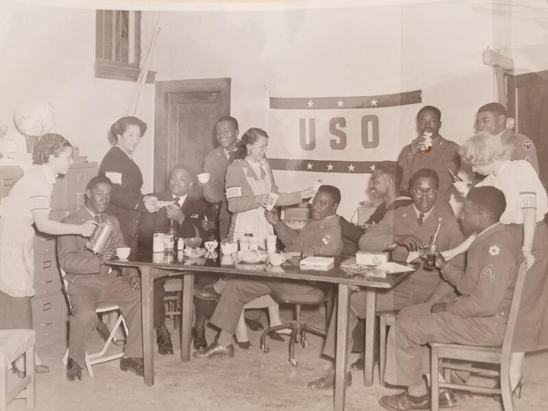 USO Women Serving Men ; several soldiers sit around a table and are served beverages