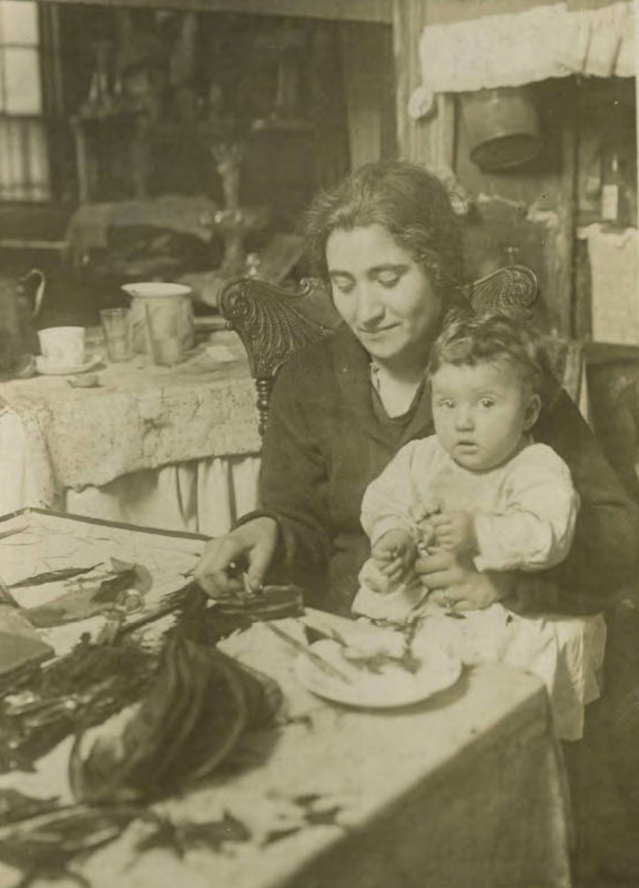Tenement Mother doing Piecework; a woman sits at a table and works while holding her baby