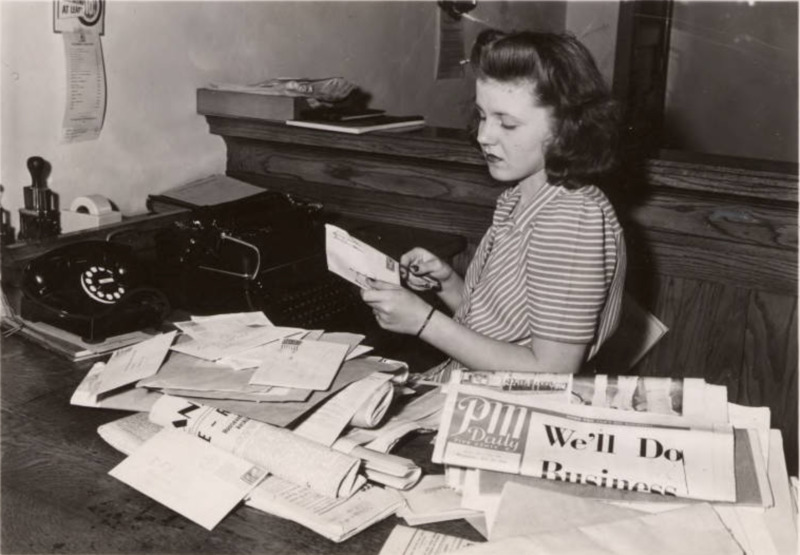 CPA employee ; woman sits at a desk opening mail