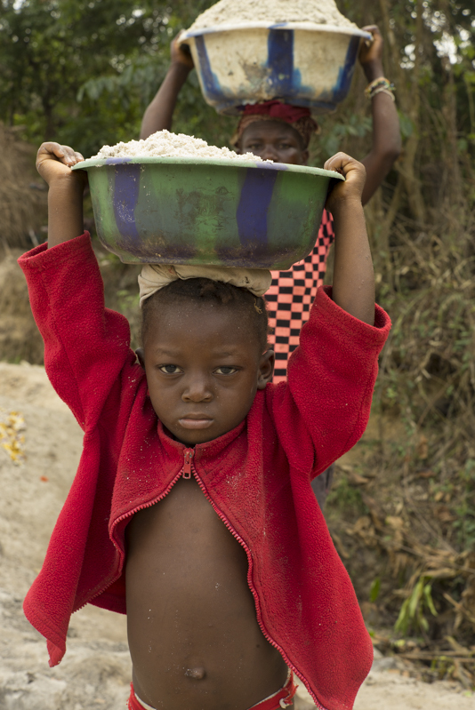 Small Child Carrying Bucket of Sand at a Diamond Mine in Tikonko Chiefdom, Sierra Leone