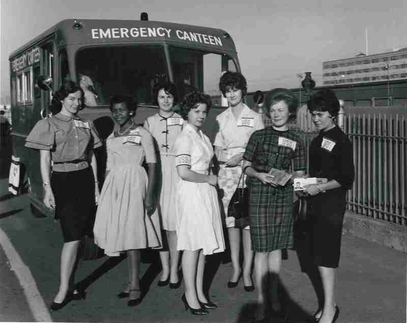 War Work Meeting Conferences delegates and canteen volunteers; YWCA USO, seven women wearing USO badges gather in front of an Emergency Canteen truck